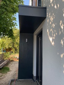 modernes Vordach mit Plattenverkleidung und seitlicher Beleuchtung