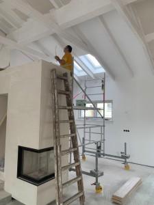Malerarbeiten im offenen Anbaubereich. Der Kamin trennt die Küche vom Wohnzimmer.